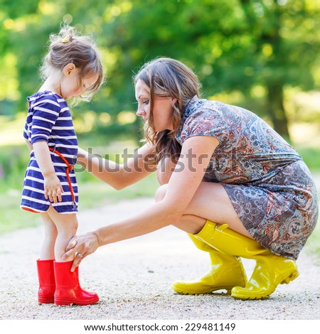 Young mother and little adorable child girl in rubber boots having fun together, family look, in summer park on sunny warm day. - stock photo