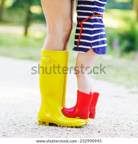 Young mother and little adorable child girl in rubber boots having fun together, family look, in summer park on sunny warm day. Long legs of woman. Square format. - stock photo