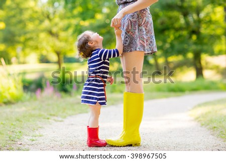 Young mother and little adorable child girl in rubber rain boots having fun together, family look. Little girl in red boots. Long legs of woman. - stock photo