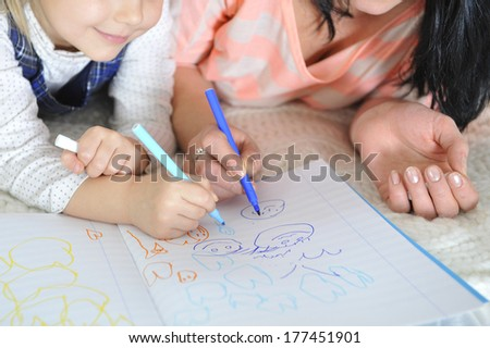 young Mother and little daughter lying and drawing together with markers having fun together - stock photo