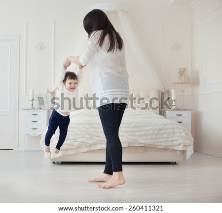 Young mother and little daughter playing in the bedroom - stock photo
