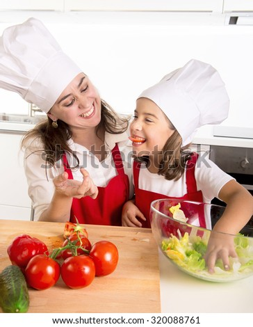 young mother and little daughter preparing salad bow playing with tomato slice in mouth wearing apron and cook hat at home kitchen having fun together in healthy vegetable nutrition concept - stock photo