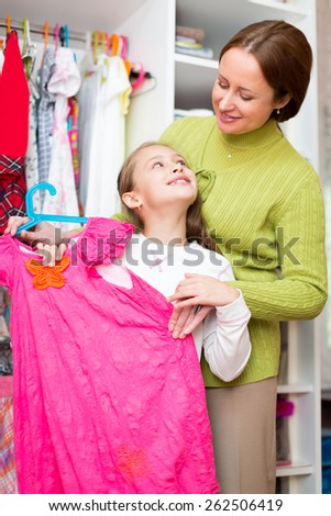 Young mother and little daughter staying near wardrobe with dresses on hangers.