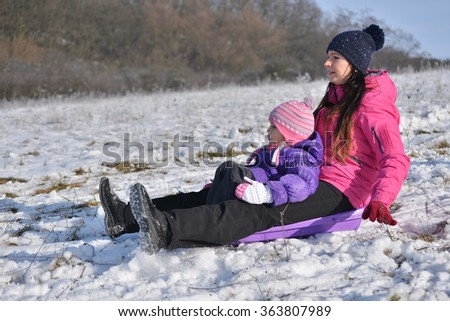 Young mother and little girl enjoying sleigh ride - stock photo