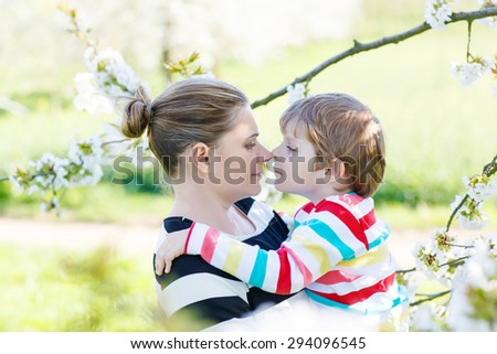 Young mother and  little kid boy having fun on blooming cherry garden in spring. Happy family enjoying nature, togetherness and celebrating mother's day. - stock photo