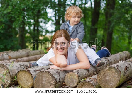 Young mother and little son having fun in summer forest