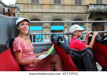 young mother and little son looking on street of Rome in tour bus in Rome, Italy, focus on mother - stock photo