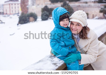 Young mother and little toddler boy having fun with snow outdoors.