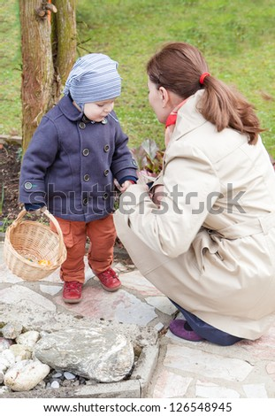 Young mother and little toddler boy on Easter Egg Hunt