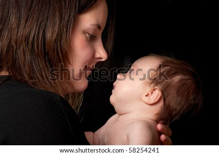 young mother and newborn baby both in profile against black