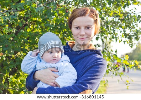Young mother and newborn baby cute outdoor portrait in autumn garden - stock photo