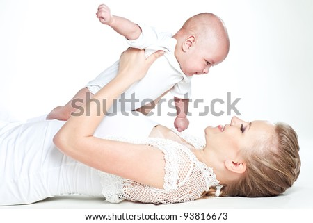 Young mother and newborn baby on a white background in the room