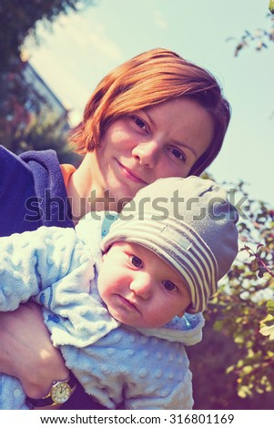 Young mother and newborn baby outdoor portrait. Vintage style toned image - stock photo