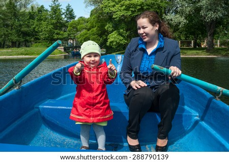 Young mother and small daughter sitting in rowboat while floating in urban park lake - stock photo