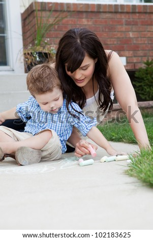 Young mother and son drawing on sidewalk with chalk - stock photo