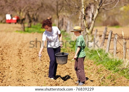 Young mother and son farmers planting seeds mixed with fertilizer - stock photo