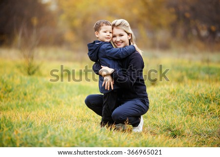 Young mother and son in autumn forest park, yellow foliage. Casual wear. Kid in blue jacket. Incomplete family, posing looking at camera positively. Childhood, children with parents are best friends. - stock photo