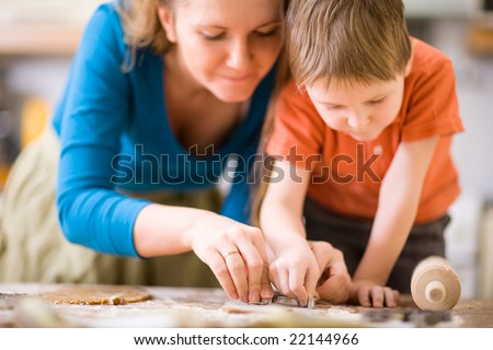 Young mother and son in kitchen making cookies.
