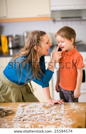 Young mother and son in kitchen making cookies. - stock photo