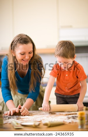 Young mother and son in kitchen making cookies. Focus on hands. - stock photo