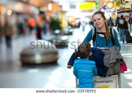 Young mother and son with luggage cart at airport - stock photo