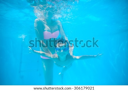 Young mother and toddler son swimming underwater in pool and having fun - stock photo