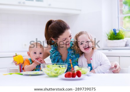 Young mother and two children cooking in a kitchen. Parent and kids cook dinner. Family with baby and toddler kid eat at home. Child preparing and eating vegetable lunch. Preschooler healthy nutrition - stock photo