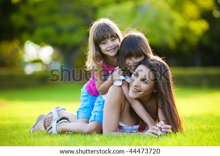 Young mother and two daughters playing in grass - stock photo