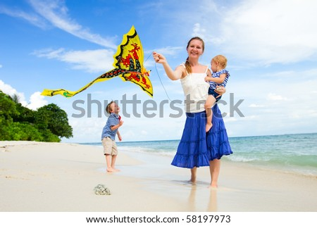 Young mother and two kids running with kite on the beach