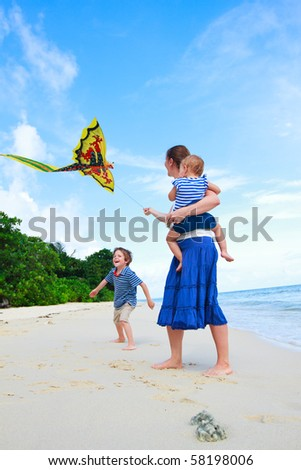 Young mother and two kids running with kite on the beach - stock photo