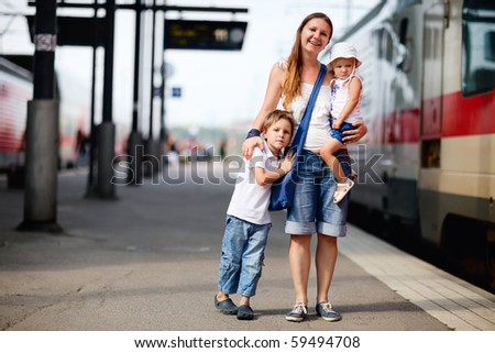 Young mother and two kids waiting for train on railway station platform - stock photo