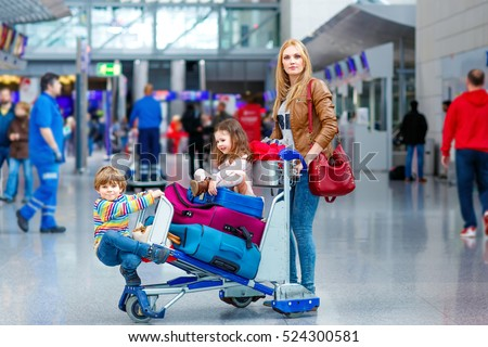 Young mother and two little kids, boy and girl, cute siblings twins at the airport. Funny children and woman, family traveling together, going on vacation via airplane and waiting with suitcases
