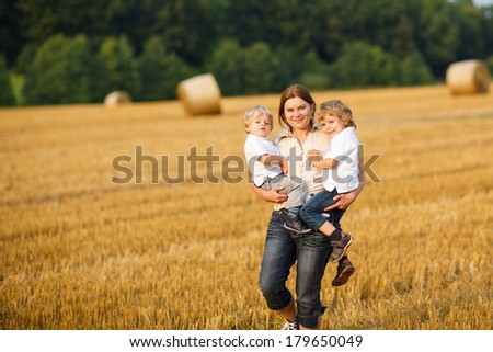 Young mother and two little twins boys having fun on yellow hay field in summer - stock photo