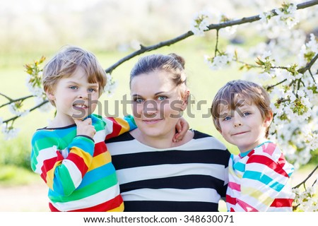 Young mother and two little twins kid boys having fun on blooming cherry garden in spring. Happy family enjoying nature, togetherness and celebrating mother's day. - stock photo