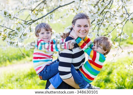 Young mother and two little twins kid boys having fun on blooming cherry garden in spring. Happy family of three enjoying nature and togetherness. - stock photo