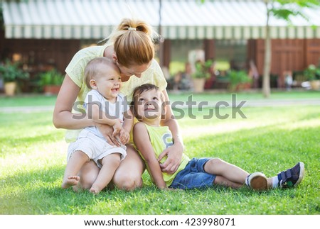 Young mother and two sons enjoying beautiful day in park - stock photo