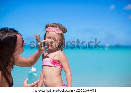 Young mother applying sunblock cream on her daughter's nose - stock photo