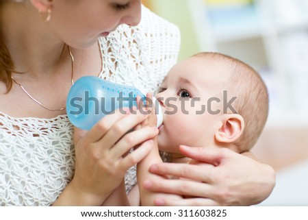 Young mother at home feeding their baby with milk bottle, feeling proud