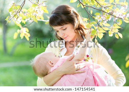 young mother breast feeding her baby girl in garden - stock photo