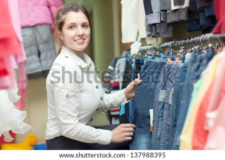 Young mother buys jeans for little child in children's clothing store - stock photo
