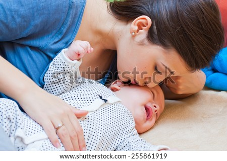 Young mother calming her crying baby boy with a kiss. - stock photo
