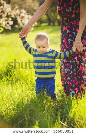 Young mother carefully holding hands of her child while baby learning to walk. Family having fun in green blooming spring garden on sunset time. Baby dressed in blue clothes and mother in long dress. - stock photo