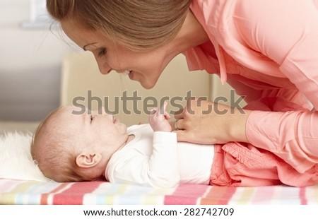Young mother caressing baby girl tenderly.