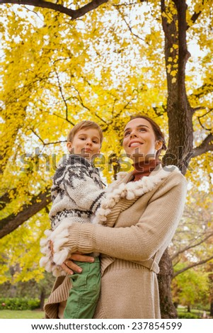 Young mother carrying her cute little son and enjoying autumn nature - stock photo