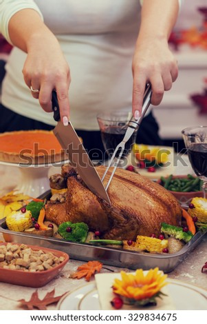 Young mother carving Thanksgiving turkey - stock photo