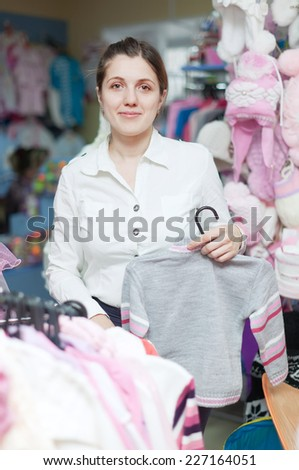 Young mother  chooses clothes for daughter at children's wear store - stock photo