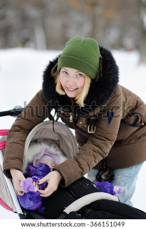 Young mother clothe warm mitten at her little daughter in winter park  - stock photo