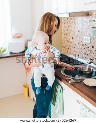 Young mother cooking and holding her baby in arms - stock photo