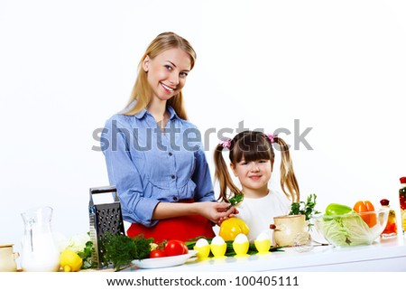 Young mother cooking fresh meal at home with her daoghter - stock photo