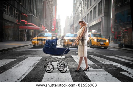 Young mother crossing a city street with a pram - stock photo